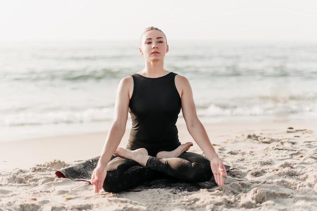 Mulher concentrada, meditando em pose de ioga na praia perto do oceano