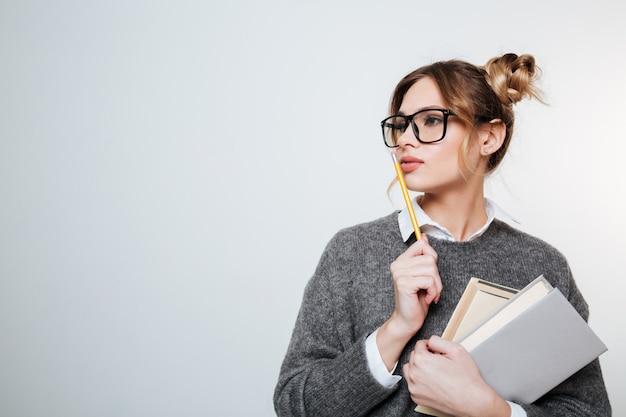 Mulher concentrada na camisola e óculos com livros