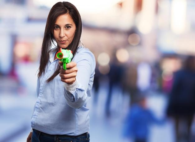 Mulher concentrada que prende um revólver de plástico
