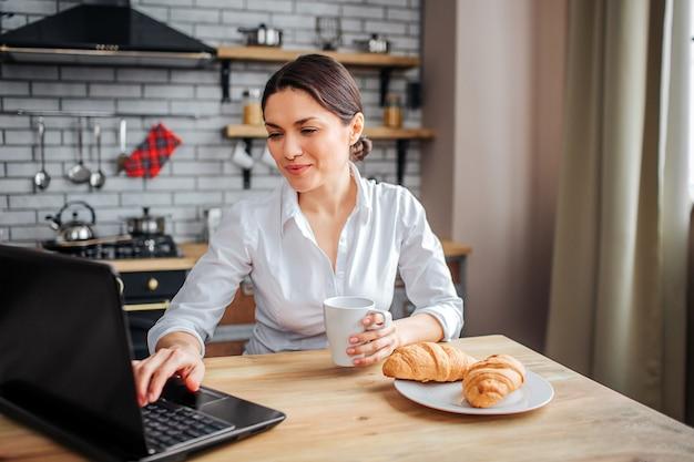 Mulher concentrada sentar à mesa na cozinha e trabalho. ela está digitando no teclado do laptop. mulher segura a mão no copo branco. croissans deitado no prato.