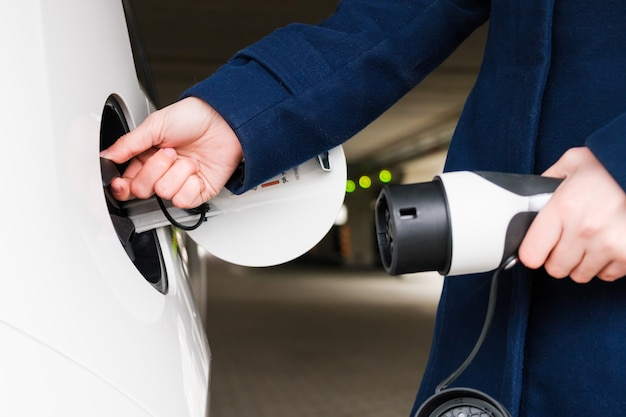 Mulher conectando a fonte de alimentação ao veículo elétrico para carregar