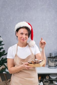 Mulher confeiteira com chapéu de ano novo e roupão de cozinha contém uma caixa de deliciosos doces e winks. quadro vertical.