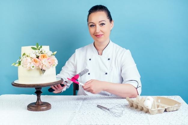 Mulher, confeiteiro, chef de confeitaria, trabalhando em um bolo de aniversário branco cremoso de duas camadas (casamento) com flores frescas em uma mesa de estúdio em um fundo azul