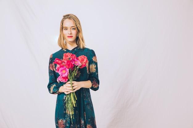 Mulher confiante atraente com buquê de flores