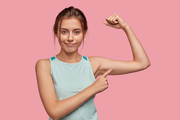Mulher confiante, bonita, morena, esportiva, com aparência agradável, levanta a mão e indica no bíceps, confirma que a mulher também pode ser forte, usa colete azul claro, isolada sobre parede rosa