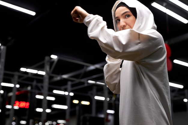 Mulher confiante boxeador muçulmano em pose de lutador, batendo, praticando esporte, boxe. na academia, centro de fitness