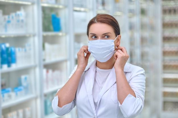 Mulher confiante com jaleco e máscara protetora