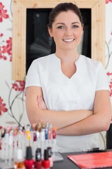 Mulher confiante com os braços cruzados na recepção no salão de uñas