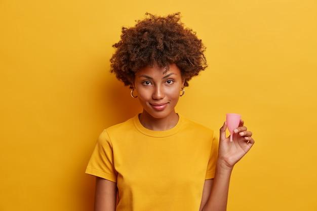 Mulher confiante copo menstrual reutilizável de silicone para mulheres durante a menstruação como alternativa aos tampões e absorventes higiênicos, informa como usar o produto de higiene feminina. melhor proteção interna