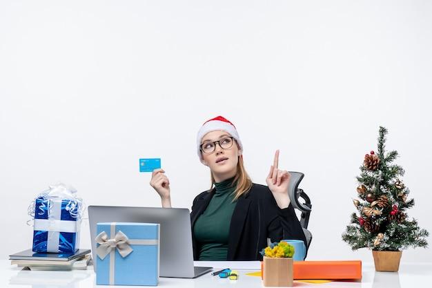 Mulher confiante e atraente com chapéu de papai noel e usando óculos, sentada à mesa, segurando o cartão do banco e apontando para cima no escritório