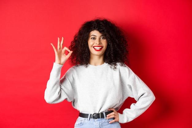 Mulher confiante e sorridente em roupas casuais, mostrando sinal de ok para aprovar ou gostar do produto, garantia de boa qualidade, fazendo um elogio, parede vermelha