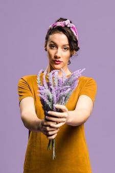Mulher confiante em vestido segurando um buquê de flores de lavanda