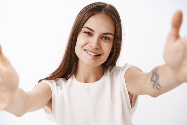 Mulher confiante, feliz, despreocupada e elegante com cabelo castanho liso e tatuagem tirando uma selfie