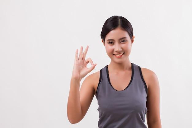 Mulher confiante feliz sorridente de aptidão fazendo gesto com a mão ok