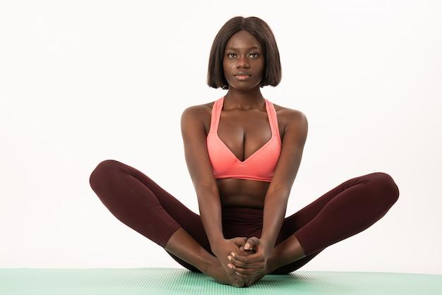 Mulher confiante fitness africano esporte fazendo exercícios de ioga