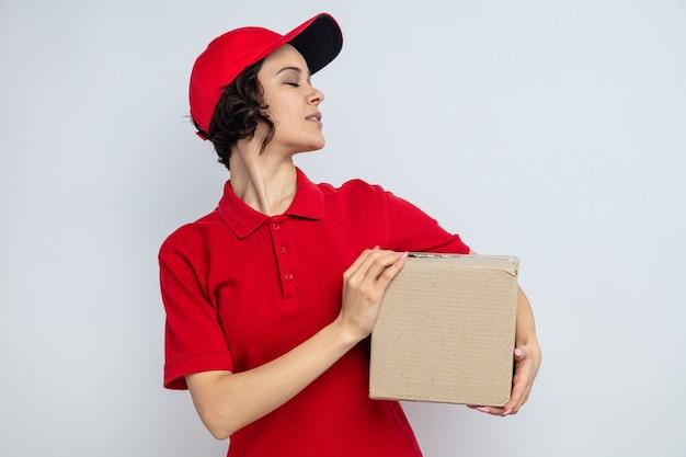 Mulher confiante, jovem e bonita, entregando uma caixa de papelão
