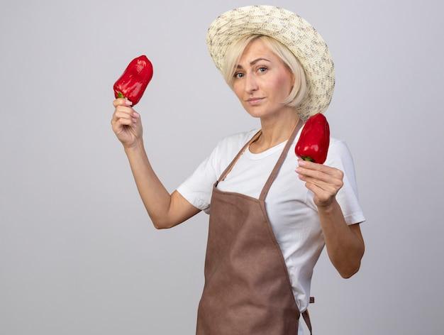 Mulher confiante, loira de meia-idade, jardineira, de uniforme, usando chapéu, em pé, segurando pimentas isoladas na parede branca.