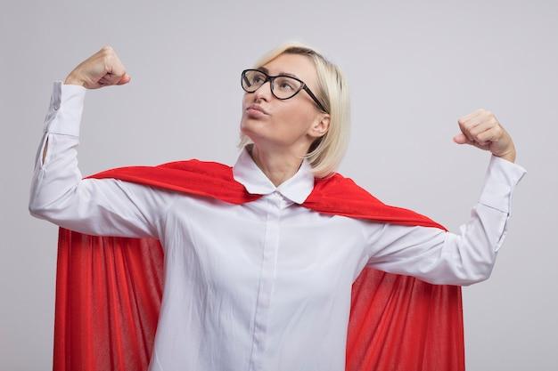 Mulher confiante loira de meia-idade, super-heroína com capa vermelha e óculos, fazendo um gesto forte, olhando para cima, isolada na parede branca