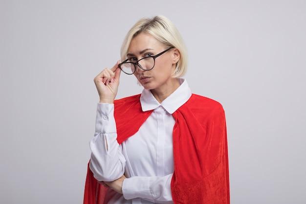 Mulher confiante loira de meia-idade, super-heroína com capa vermelha usando e agarrando os óculos