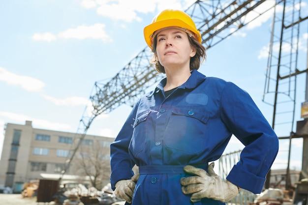 Mulher confiante posando no canteiro de obras