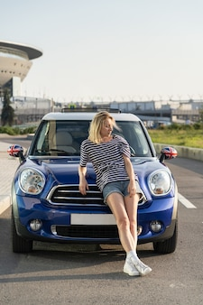 Mulher confiante, proprietária de um automóvel em um carro moderno do lado de fora dos prédios urbanos do centro de uma concessionária de automóveis