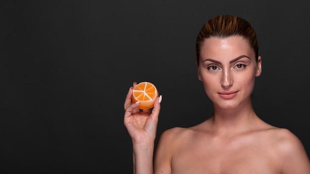 Mulher confiante segurando o produto de cuidados da pele