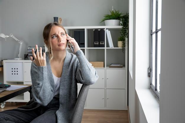 Mulher confusa de tiro médio falando ao telefone