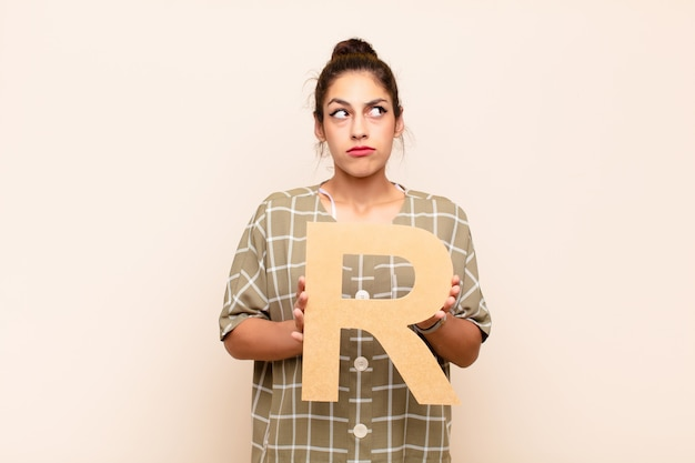 Mulher confusa, duvidosa, pensativa, segurando a letra r do alfabeto para formar uma palavra
