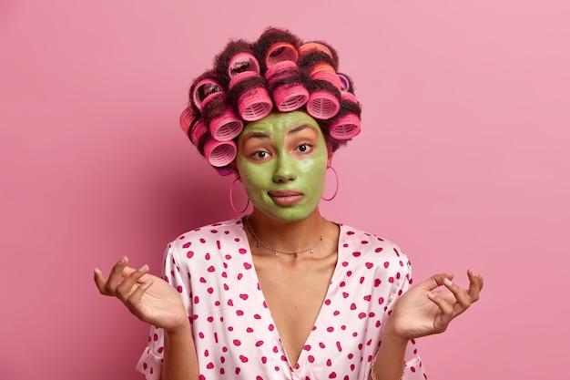 Mulher confusa e inconsciente estende as mãos para os lados, enfrenta dilemas, aplica máscara facial verde para ficar bonita, usa modeladores de cabelo para um penteado perfeito, vestida com robe de seda, hesita sobre algo
