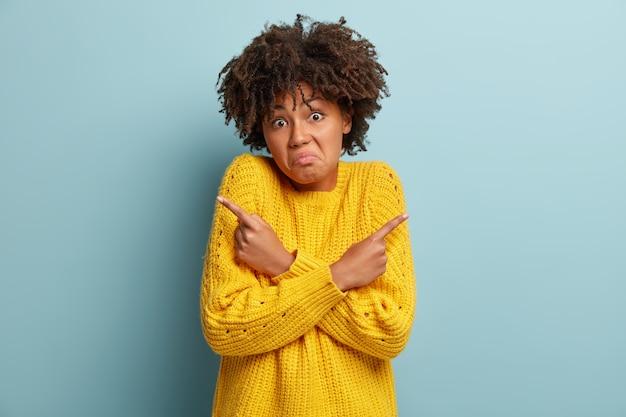 Mulher confusa e sem noção aponta para cantos diferentes, sente-se em dúvida e inconsciente, toma uma decisão, usa um macacão amarelo de malha, franze a testa, fica de pé sobre uma parede azul. conceito de pessoas e percepção