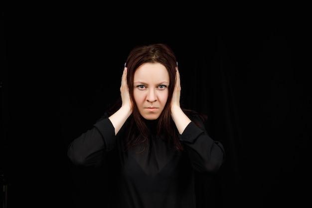 Mulher confusa, segurando as mãos na cabeça sobre o fundo preto do estúdio. retrato de jovem sério, fechando os ouvidos, não ouve nenhum mal, conceito de surdez, copie o espaço.