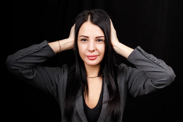 Mulher confusa, segurando as mãos na cabeça sobre o fundo preto do estúdio. retrato de jovem sério, fechando os ouvidos, não ouve nenhum mal, o conceito de surdez, copie o espaço.