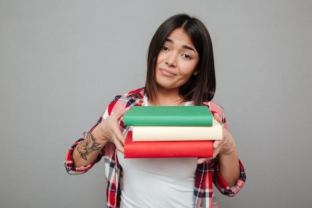 Mulher confusa segurando muitos livros sobre parede cinza