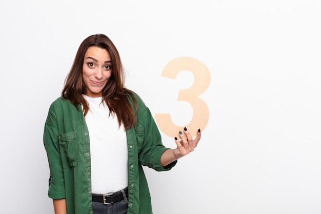 Mulher confusa segurando um número 3