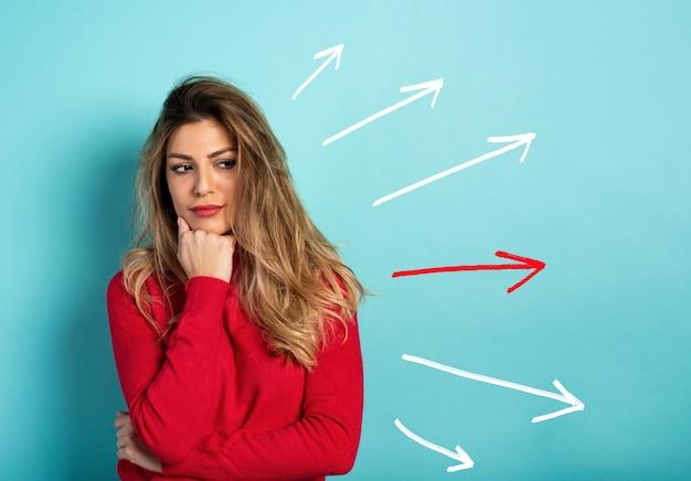 Mulher confusa tem que escolher a seta direita a seguir. conceito de opções, confusão, decisão.