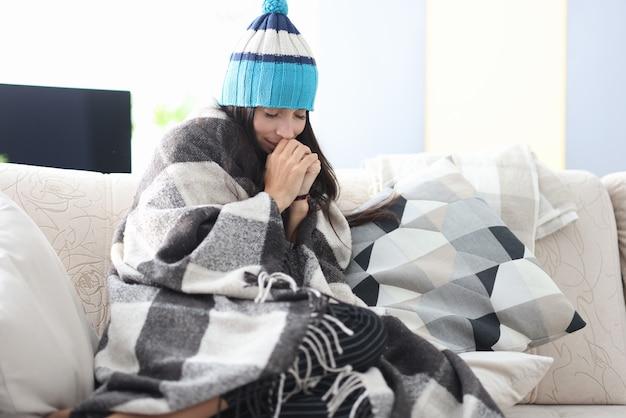 Mulher congelada com chapéu e cobertor sentada no sofá