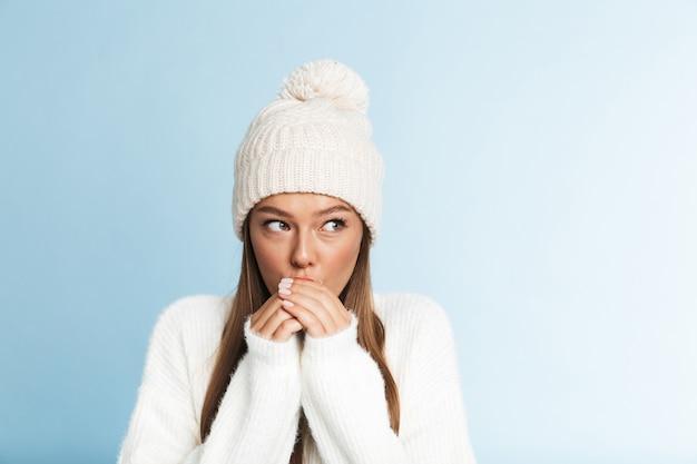 Mulher congelada com chapéu e suéter em pé