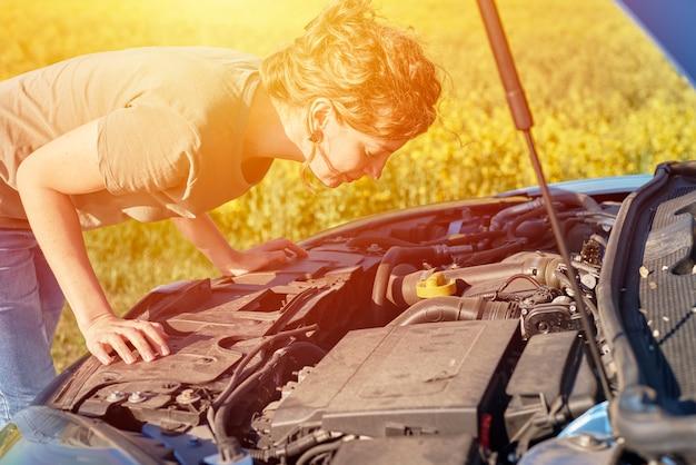 Mulher conserta carro quebrado com o capô aberto na estrada