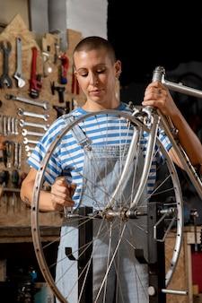 Mulher consertando bicicleta tiro médio