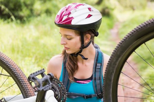 Mulher consertando sua bicicleta