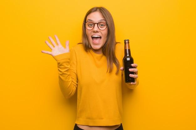 Mulher consideravelmente caucasiano dos jovens que comemora uma vitória ou um sucesso. ela está segurando uma cerveja.