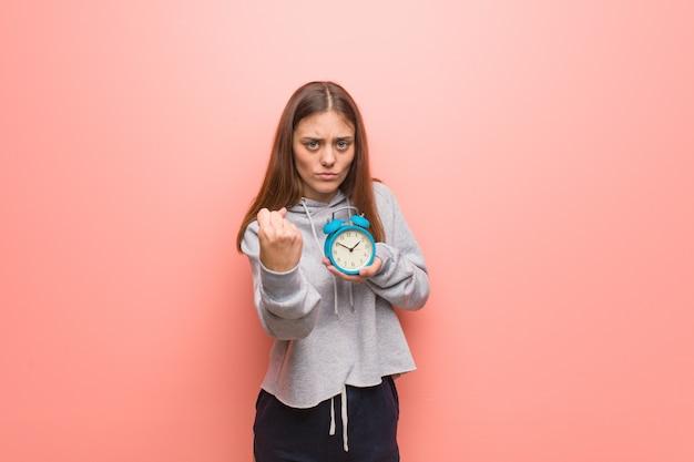 Mulher consideravelmente caucasiano dos jovens que mostra o punho para frontear, expressão irritada. ela está segurando um despertador.