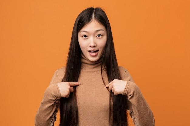 Mulher consideravelmente chinesa dos jovens surpreendida apontando dsi mesmo, sorrindo amplamente.