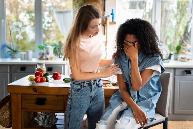 Mulher consolando amigas tristes na cozinha