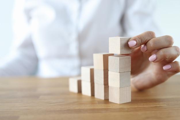 Mulher construir torre de cubos de madeira na mesa. crescimento de carreira subindo escadas