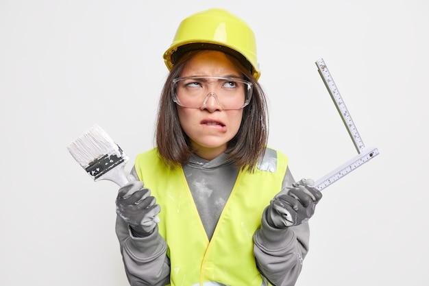 Mulher construtor faz reconstrução de casa morde lábios segura pincel de pintura e fita métrica usa ferramentas de construção usa capacete óculos de segurança colete reflexivo. conceito de manutenção