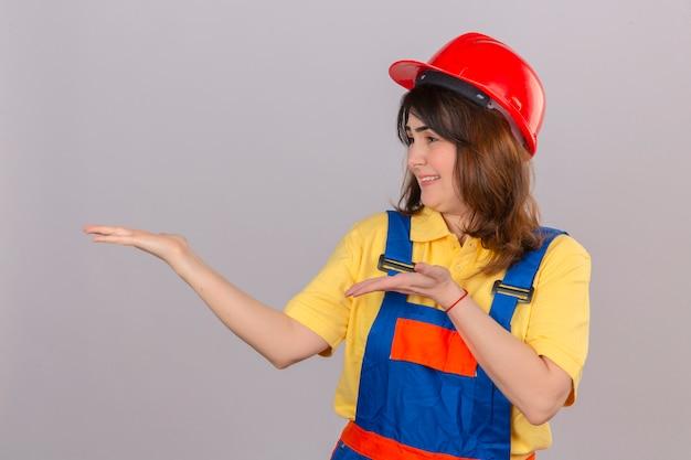 Mulher construtor no uniforme de construção e capacete de segurança, apresentando e apontando com as palmas das mãos, sorrindo alegremente sobre parede branca isolada