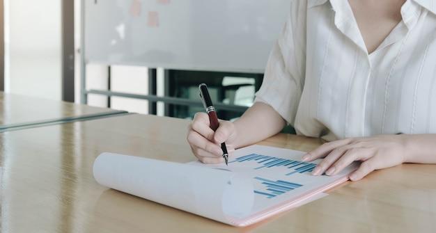 Mulher, consultora de investimentos, analisando o balanço patrimonial do relatório financeiro anual da empresa, trabalhando com gráficos de documentos.