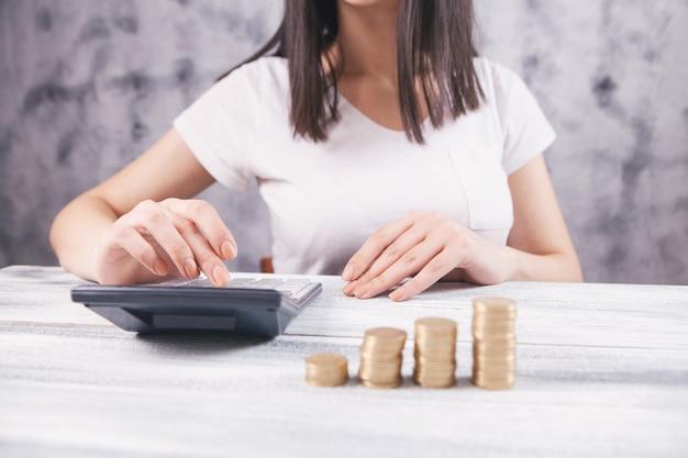 Mulher conta com calculadora e moedas na mesa