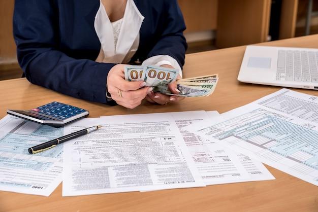 Mulher conta dinheiro preenchendo formulários fiscais